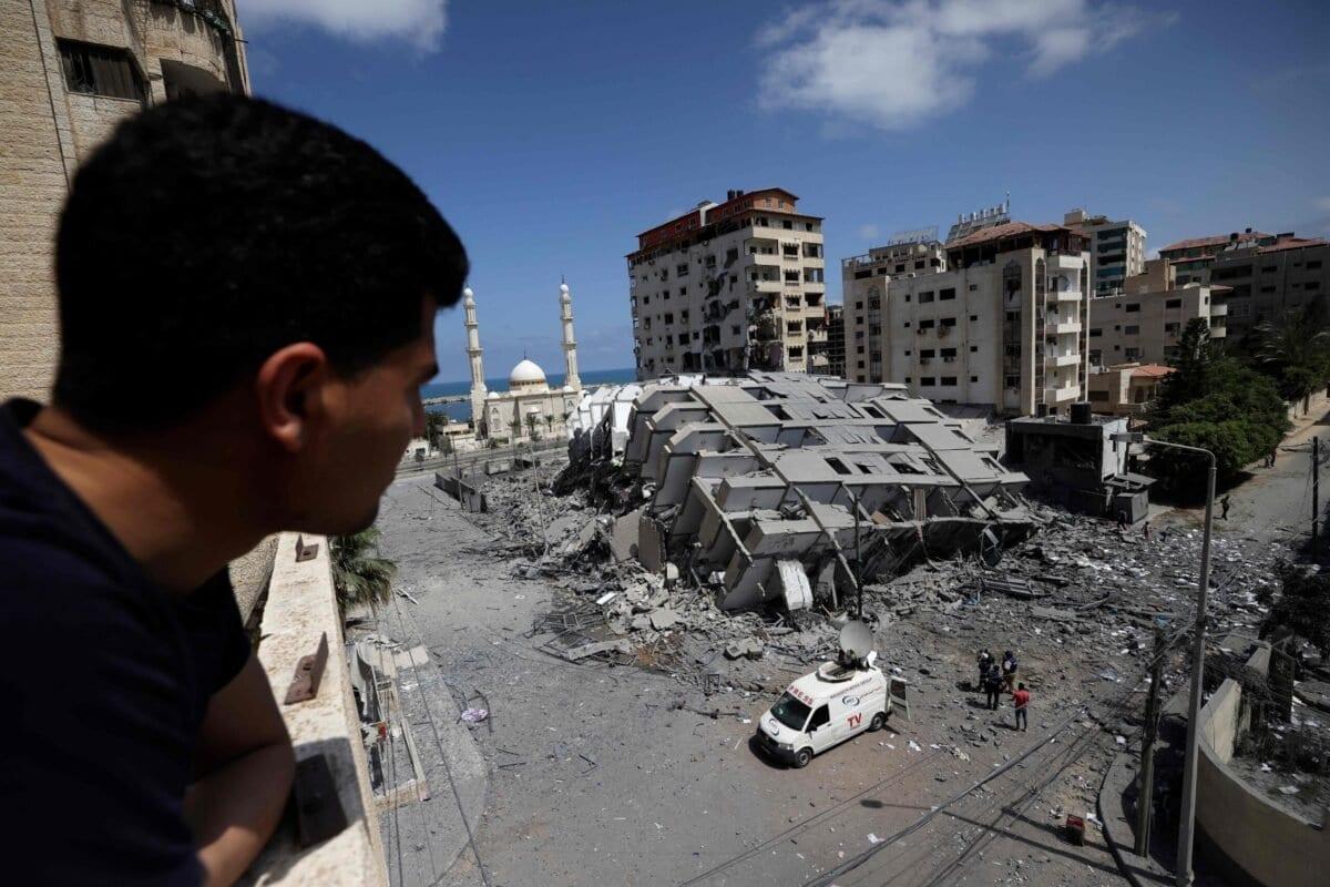 Um homem palestino olha para um prédio destruído na Cidade de Gaza, após uma série de ataques aéreos israelenses na Faixa de Gaza controlada pelo Hamas, em 12 de maio de 2021 [Mohammed Abed/AFP via Getty Images]