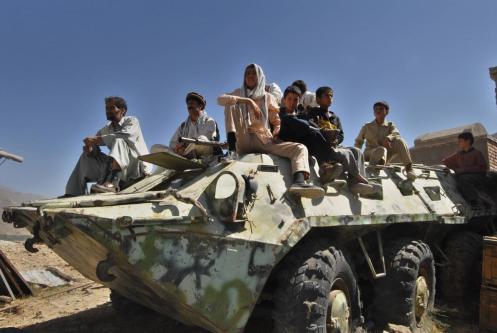 Afegãos sentam-se sobre um tanque soviético abandonado no Vale do Panjshir, em 10 de setembro de 2006 [Shah Marai/AFP via Getty Images]
