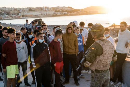 Soldado espanhol conversa com jovens refugiados deportados ao Marrocos, em 19 de maio de 2021 [Diego Radamés/Agência Anadolu]