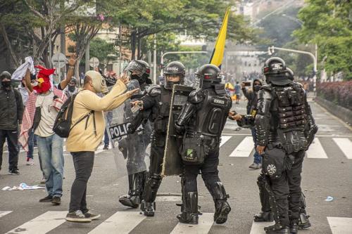 Manifestante com máscara contra gás lacrimogênio pede calma à polícia durante a greve geral de 28 de abril [Colombia Informa]