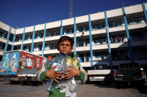 Garoto palestino segura garrafas vazias enquanto procura um lugar para enchê-las com água potável, em Gaza, em 15 de maio de 2021 [UNICEF/Eyad El Baba]