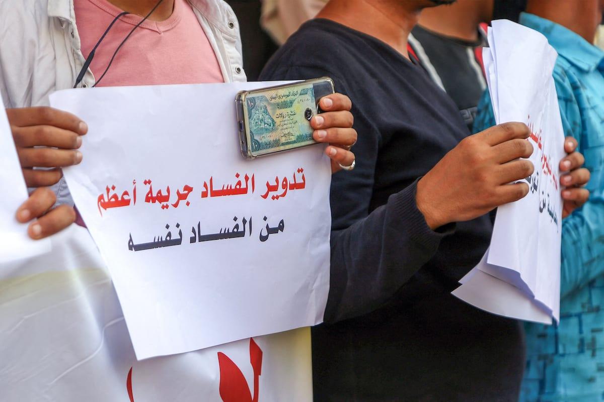 Homem iemenita exibe dinheiro e cartaz em árabe contra a corrupção, durante protesto na cidade de Taez, Iêmen, 3 de junho de 2021 [Ahmad al-Basha/AFP via Getty Images]