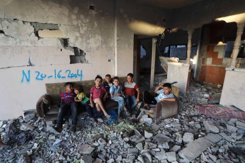 Crianças palestinas em meio aos escombros de um edifício danificado por ataques israelenses em Beit Lahia, na Faixa de Gaza, 7 de junho de 2021 [Ashraf Amra/Agência Anadolu]