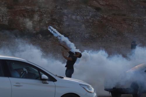 Forças israelenses atiram gás lacrimogêneo contra palestinos que protestam pela libertação da ex-legisladora do Conselho Legislativo Palestino (PLC) Khalida Jarrar, em frente à prisão de Ofer em Ramallah, Cisjordânia, em 12 de julho de 2021 [Issam Rimawi/Agência Anadolu]