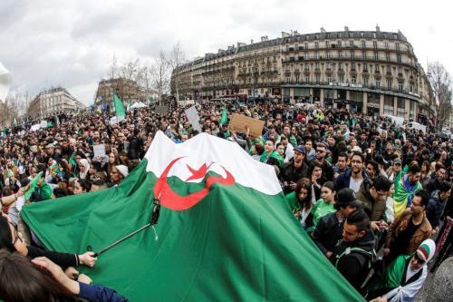 Manifestantes agitam bandeiras argelinas durante protesto sobre temores de conspiração para prolongar o governo do presidente argelino, na Place de la Republique (Praça da República) em Paris, em 24 de março de 2019 [FRANCOIS GUILLOT/AFP/Getty]