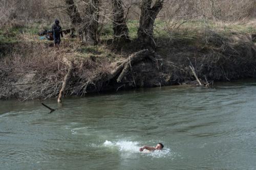 Refugiado nada no rio Evros após dois dias isolado em uma ilha fluvial, na região de Erdine, fronteira entre Turquia e Grécia, 1° de março de 2020 [Burak Kara/Getty Images]