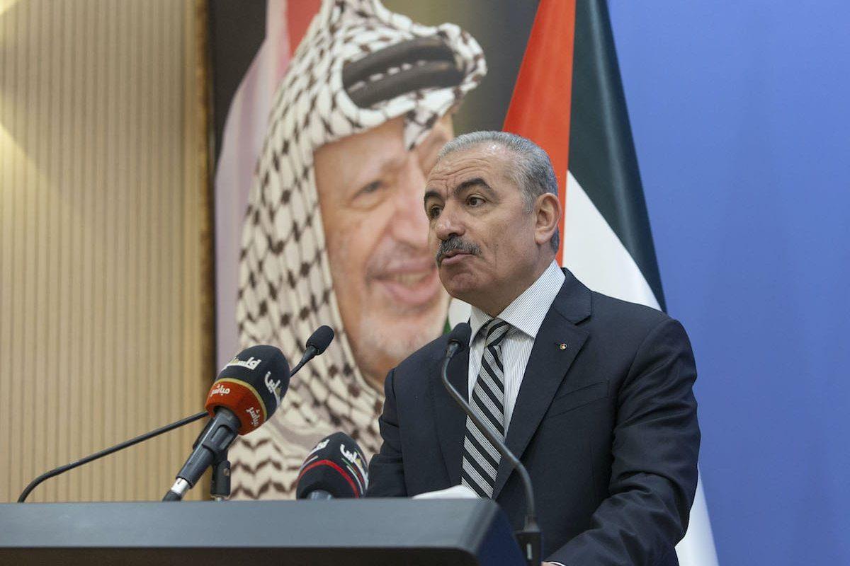 O primeiro-ministro palestino Muhammad Shtayyeh preside a reunião de gabinete semanal em seu escritório perto de um pôster do falecido líder palestino Yasser Arafat na cidade de Ramallah, na Cisjordânia, em 17 de agosto de 2020. [Nasser Nasser/ Pool/ AFP via Getty Images]