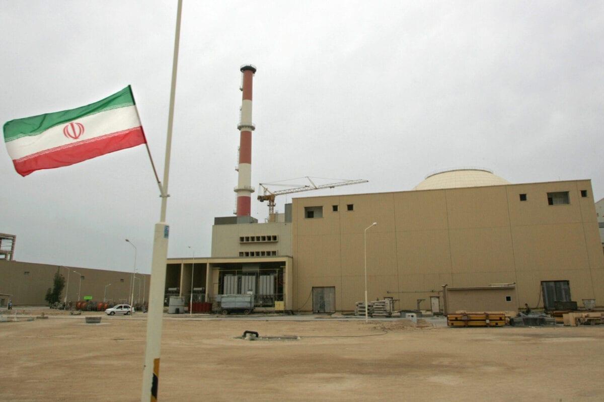 Foto de arquivo datada de 3 de abril de 2007 mostra uma bandeira iraniana fora do prédio que abriga o reator da usina nuclear de Bushehr na cidade portuária de Bushehr, no sul do Irã, 1200 km ao sul de Teerã [Behrouz Mehri/AFP via Getty Images]