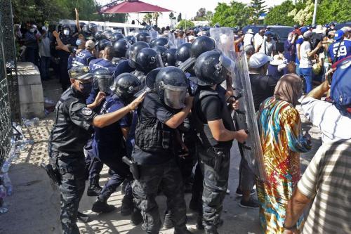Oficiais de segurança tunisianos bloqueiam os manifestantes em frente ao prédio do parlamento na capital Túnis, em 26 de julho de 2021, após o presidente suspender o parlamento do país e demitir o primeiro-ministro. [FETHI BELAID/AFP via Getty Images]