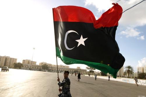 Um homem líbio agita sua bandeira nacional em Benghazi, Líbia, em 27 de fevereiro de 2015 [Abdullah Doma/AFP/Getty Images]