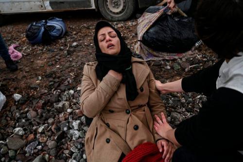 Mulher reage à chegada de um bote improvisado com 54 refugiados afegãos na ilha de Lesbos, Grécia, 28 de fevereiro de 2020 [Aris Messinis/AFP via Getty Images]
