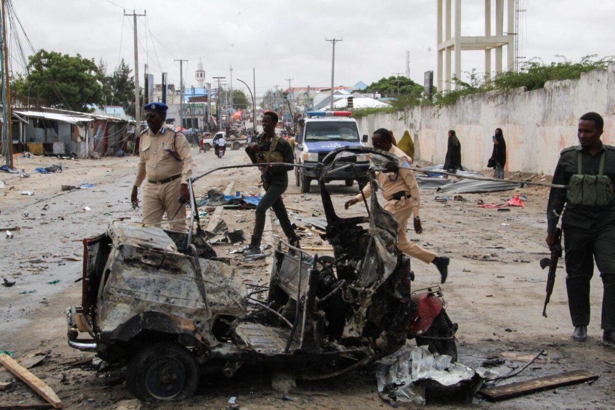 Policiais patrulham os destroços de um carro na cena do ataque suicida com carro-bomba que teve como alvo o comissário de polícia da cidade em Mogadíscio, em 10 de julho de 2021 [AFP via Getty Images]