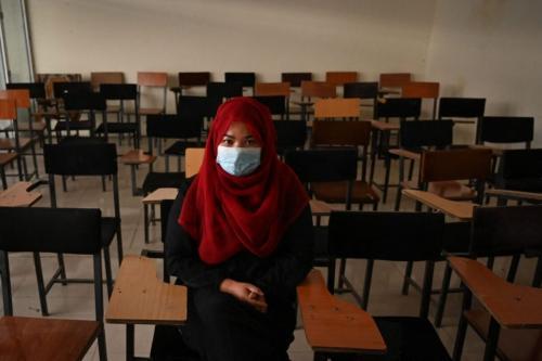 Uma estudante está sentada dentro de uma sala de aula depois que universidades particulares reabriram em Cabul em 6 de setembro de 2021. Mulheres que frequentam universidades privadas afegãs devem usar um manto abaya e niqab cobrindo a maior parte do rosto, ordenou o Talibã, e as aulas devem ser segregadas por sexo - ou pelo menos divididas por uma cortina [Aamir Quereshi/AFP via Getty Images]