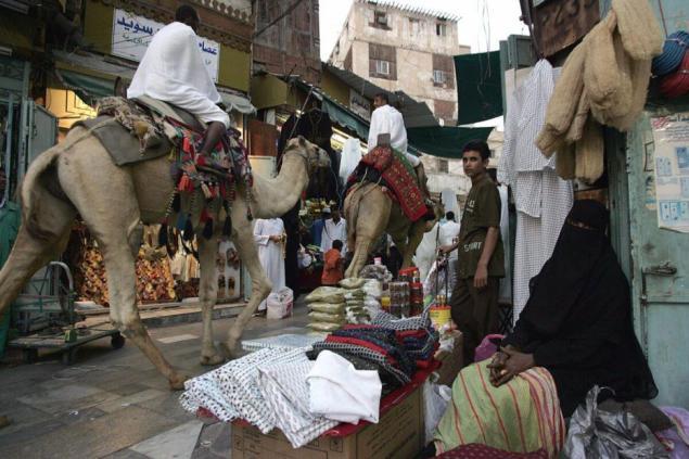 Peregrinos muçulmanos andam de camelo em um mercado na Cidade Velha de Jeddah, 14 de janeiro de 2005 [Karim Sahib/AFP via Getty Images]