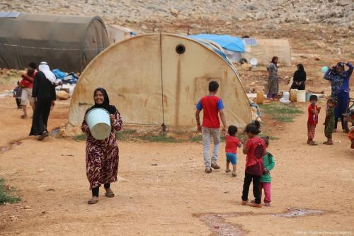 Mulher síria carrega balde para encher de água, às vésperas do feriado islâmico do Eid, em Idlib, norte da Síria, 23 de junho de 2017 [Ismihan Özgüven/Agência Anadolu]