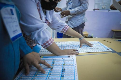 Funcionários da comissão eleitoral começam a contar cédulas em uma mesa de votação após o término das eleições gerais antecipadas em Bagdá, Iraque, em 10 de outubro de 2021 [Ayman Yaqoob/Agência Anadolu]