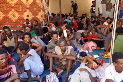 Imigrantes ilegais ficam dentro do abrigo de Ganzour após serem transferidos da estrada do aeroporto devido aos combates na capital líbia, Trípoli, em 5 de setembro de 2018 [MAHMUD TURKIA/AFP/Getty Images]