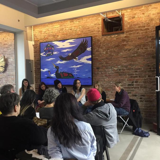 Panelist of Literary Gatekeepers and Accountability sit in a row in front of audience against brick wall with Indigenous art