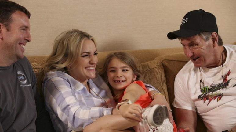 Jaimie Lynn holds Maddie on couch in hotel before Opry show.