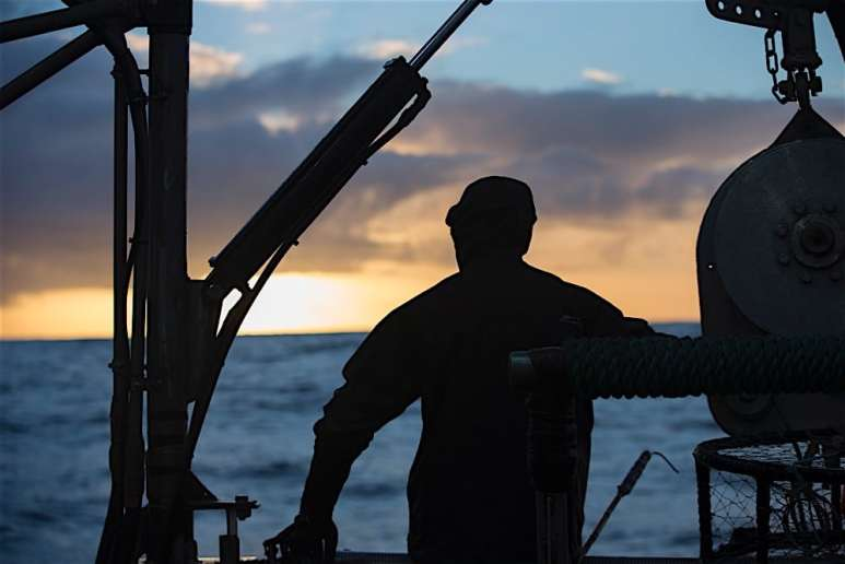 Deckhand pictured as the sun sets on another tough day