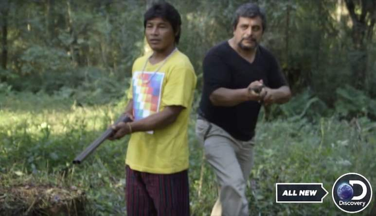 The two men point guns at the Treasure Quest: Snake Island team and camera crew