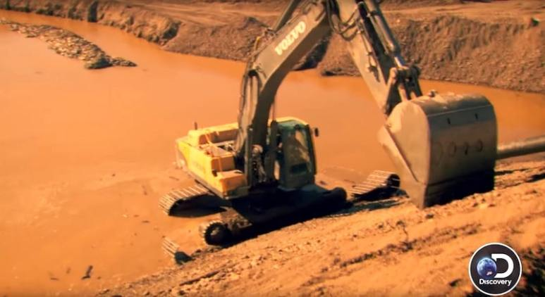 The excavator lies stuck in the mud after the track snaps