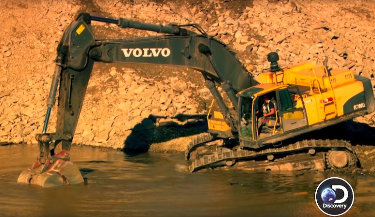 Brennan drives the excavator into the water as the others look on