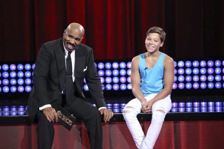 Steve Harvey sitting on stage with Svyatoslav Rasshivkin on Little Big Shots