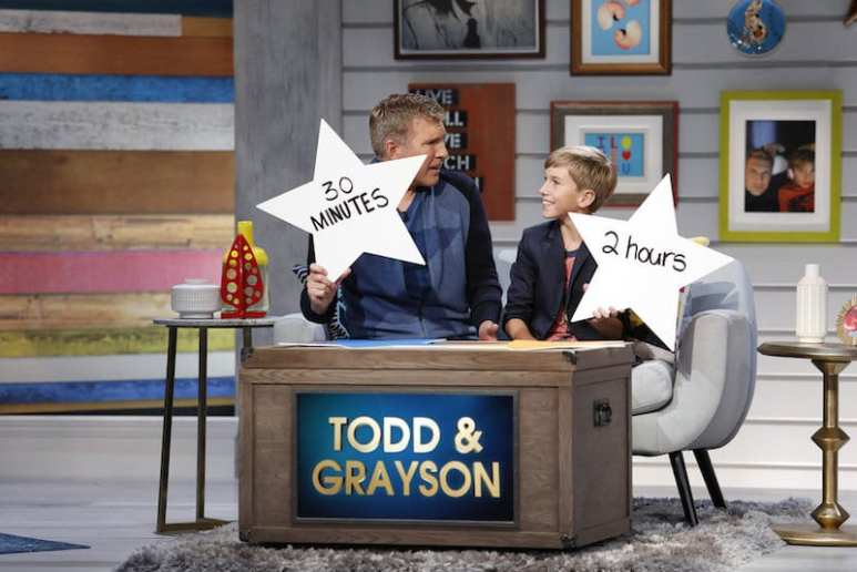 Todd Chrisley and son Grayson holding up stars with the answers they have written on them
