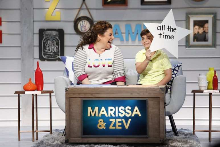 Marissa Jaret Winokur and son Zev sitting together on the show, as he holds up a star