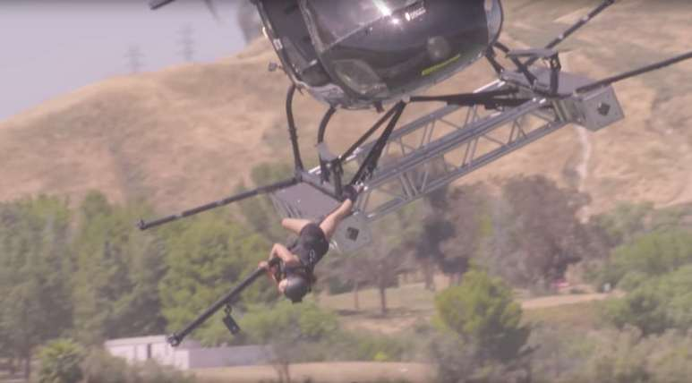 A woman climbs underneath a helicopter