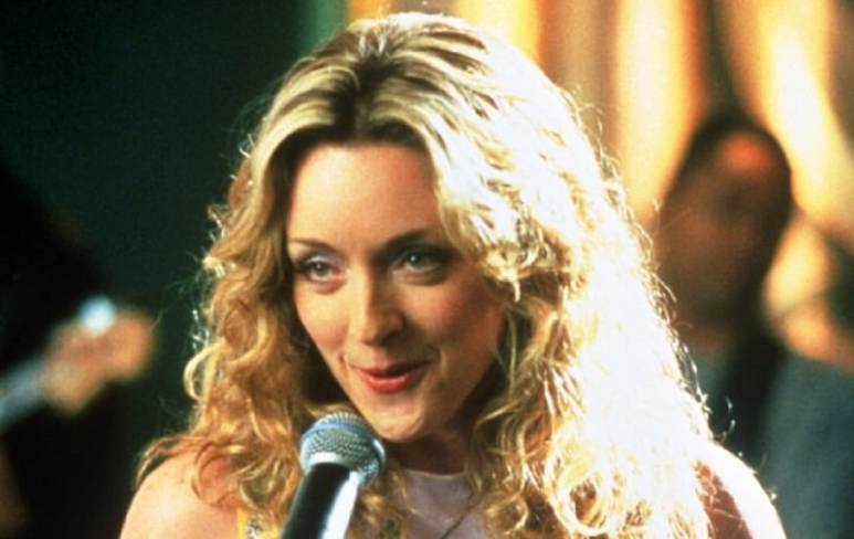 Jane Krakowski speaking into a microphone as Elaine Vassal in Ally McBeal