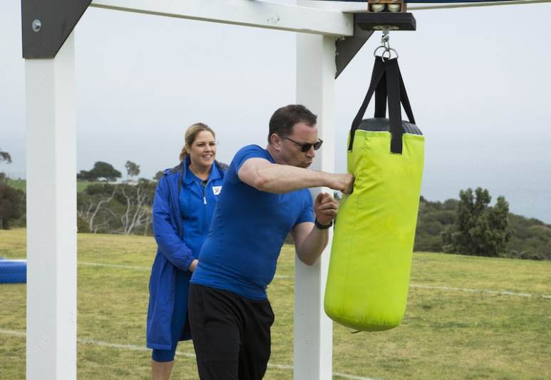 Mary McCormack looks on as Joshua Malina hits a punching bag
