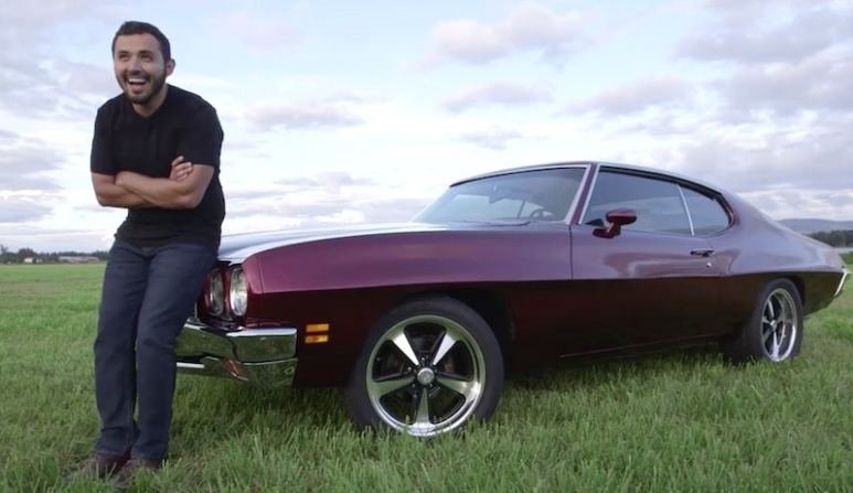 Carlos from Carspotting leaning on a classic muscle car