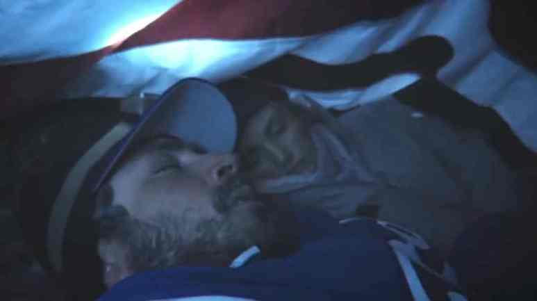Actors playing Kenny Pasten and Tiffany Finney sheltering under the American flag on In an Instant