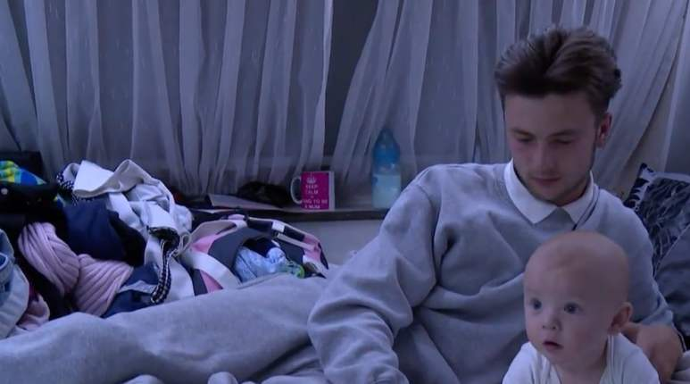 Dylan lying at home with the baby