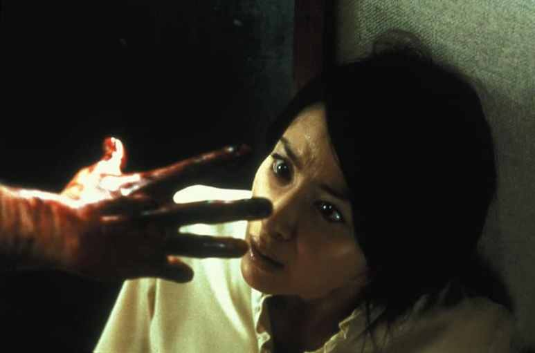 Megumi Okina cowers away from a bloodied hand in Ju-on: The Grudge