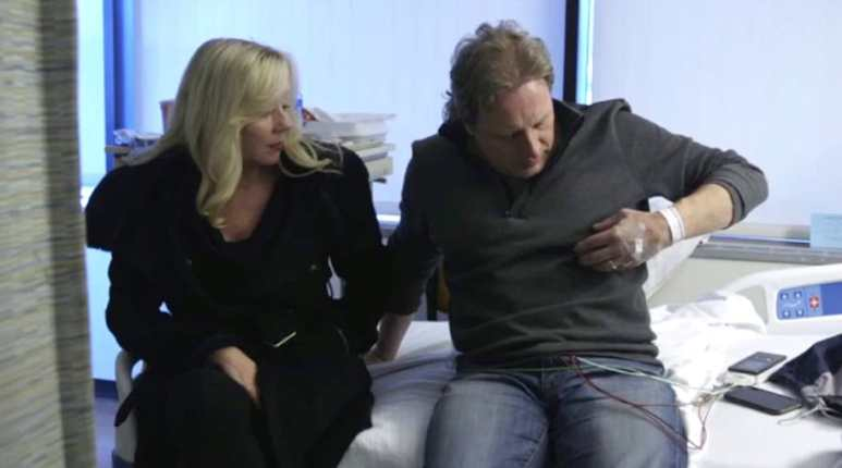 Sig sitting on a hospital bed with wife June while touching his chest on Deadliest Catch