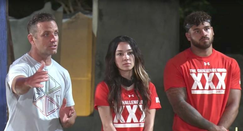 TJ Lavin standing next to players Briana and Cory on The Challenge XXX: Dirty Thirty