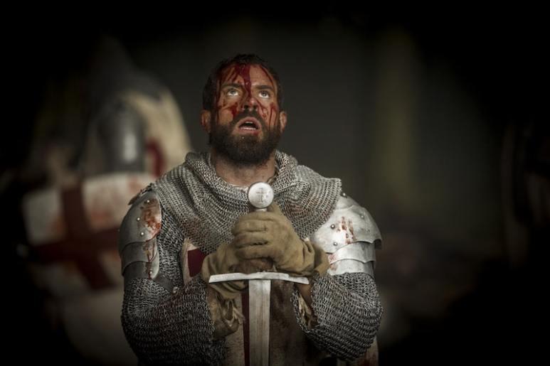 Templar Knight Landry (Tom Cullen) bowed before his sword from HISTORY's New Drama Series Knightfall.