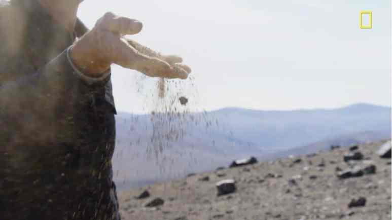 Phil Keoghan shows how arid the Atacama Desert soil is. Pic credit: Nat Geo