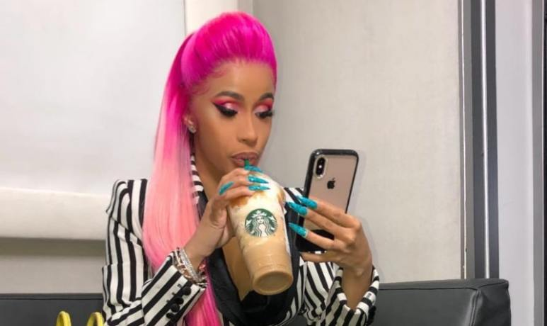 Cardi B sipping on Starbucks and checking her phone
