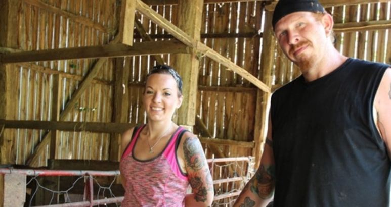 Chico and Sondra smiling in a barn in a still from Discovery's Moonshiners