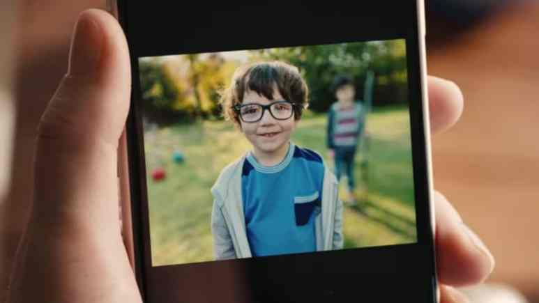 Little boy on the iPhone screen during bokeh demonstration