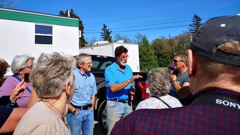 Craig Tester and Rick Lagina talk to people on an Oak Island tour