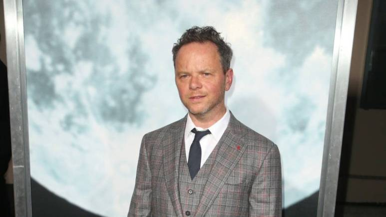 Noah Hawley posing in front of picture of the moon