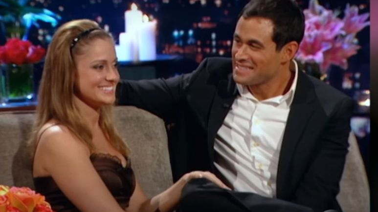 Jason Mesnick in a suit sits on The Bachelor couch with Molly Malaney in a silk dress with her hair in a headband