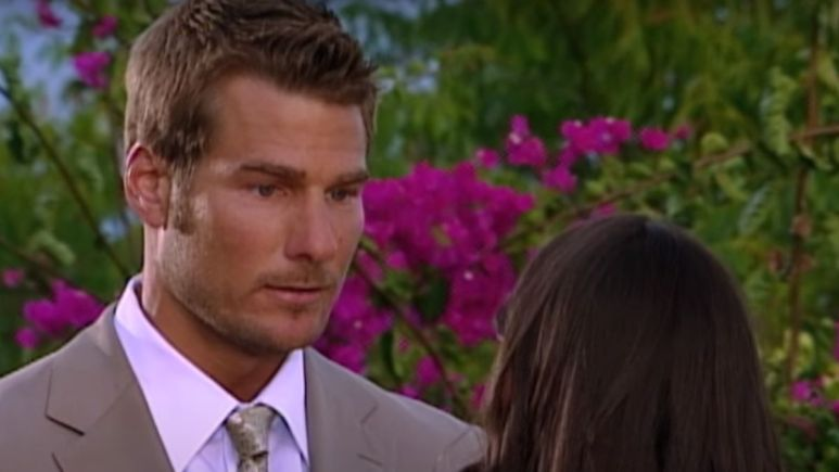 Brad Womack in a tan suit looking serious with the back of Deanna Pappas head in the background