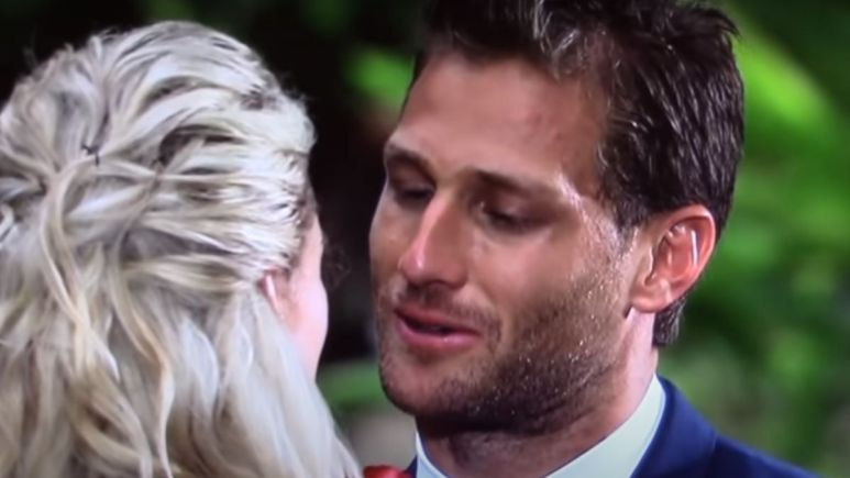 Juan Pablo Galavis holds a rose with the back of Nikki Ferrell's head in the background