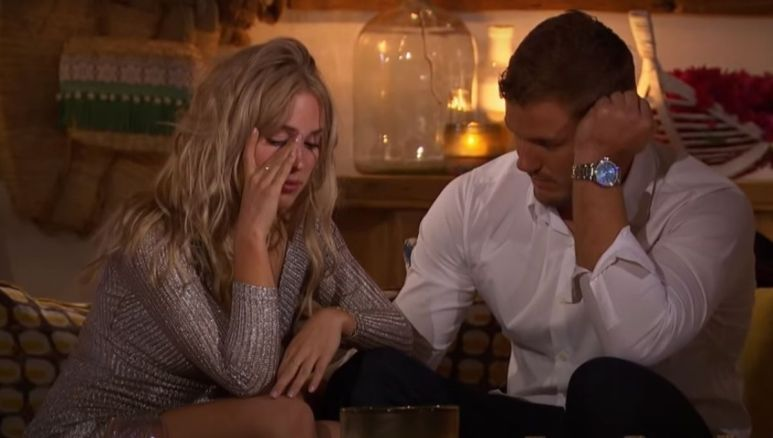 Cassie Randolph in a silver dress talking to Colton Underwood in white shirt